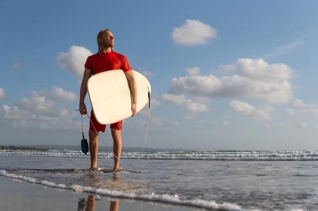 Surfista che cammina lungo la spiaggia. bali