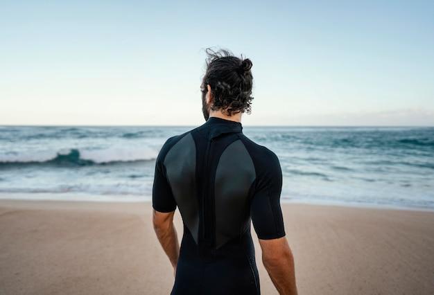 Surfer che cammina lungo l'oceano da dietro il colpo