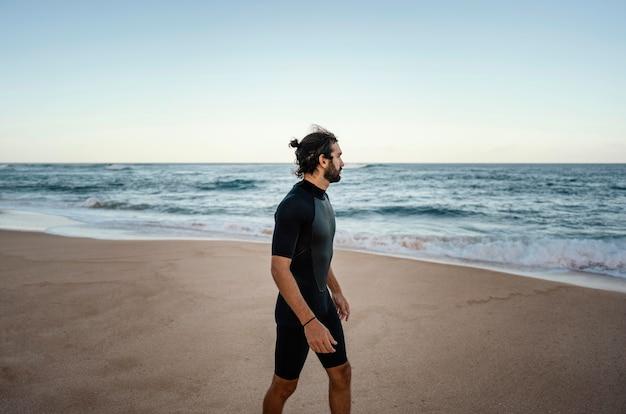 Surfista che cammina lungo l'oceano