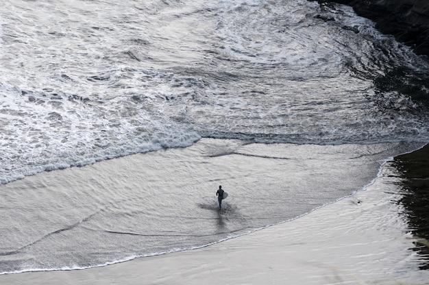 ニュージーランドでサーフボードを持って海に足を踏み入れるサーファー
