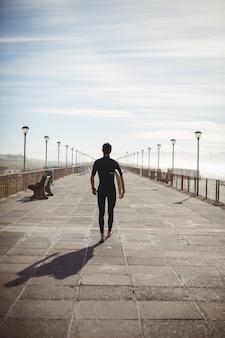 Surfista che cammina con la tavola da surf