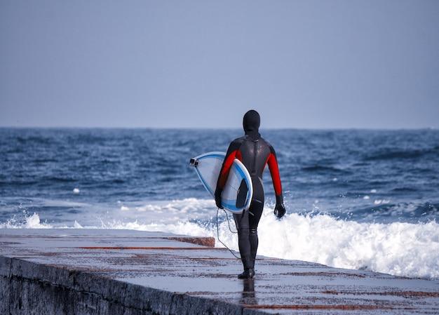 Зимой серфер идет в океан в гидрокостюме. холодный серфинг. всплеск волны. водонепроницаемый костюм
