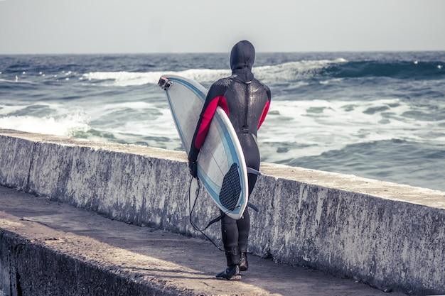 Зимой серфер заходит в воду в гидрокостюме.