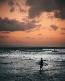 A surfer wearing surfing swimsuit holding a surfboard standing at the seashore during sunset