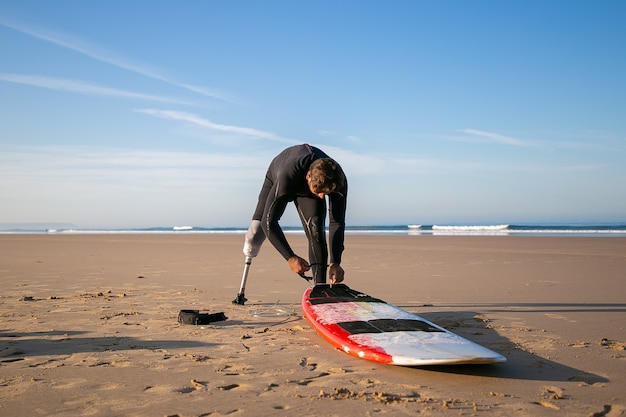 Surfer wearing wetsuit and artificial limb, tying board to his ankle on sand