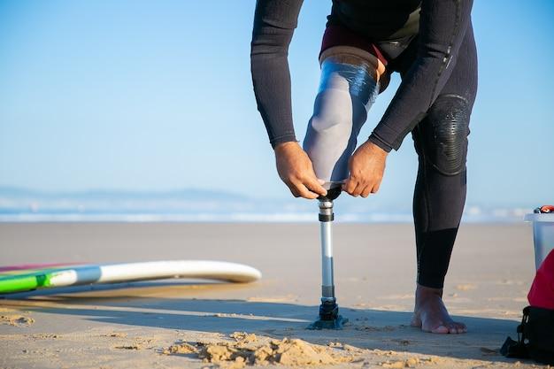 Surfer che indossa la muta, in piedi vicino alla tavola da surf sulla sabbia e regolando l'arto artificiale fissato con nastro adesivo alla gamba
