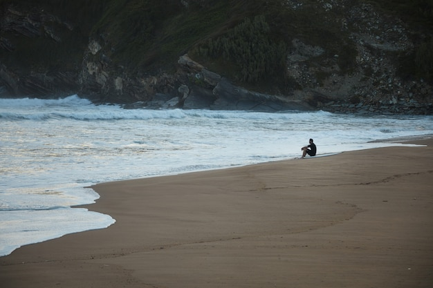 Surfer in wetsuit sitting at the edge of a sandy beach under a green and rocky hill in the evening