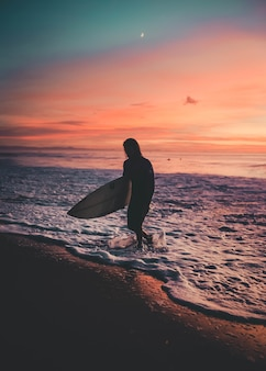 Surfer with a board walking out of the sea during sunset
