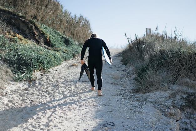 Серфер с ластами и бордюром в гидрокостюме на берегу океана