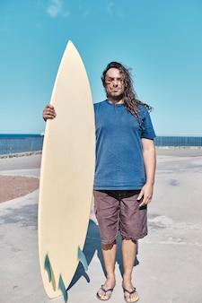長い髪を持つサーファーは彼のサーフボードを保持します
