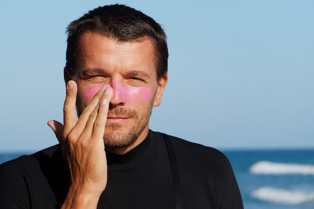 Surfer with pink sunscreen on his face. tropical beach. active lifestyle.