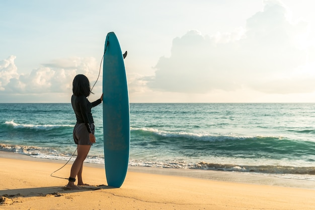 Surfer woman carrying their surfboards on sunset beach with sun light