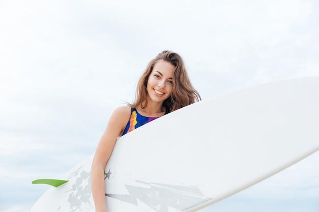 Молодая девушка серфера с сексуальным подтянутым телом в купальнике держит доску для серфинга