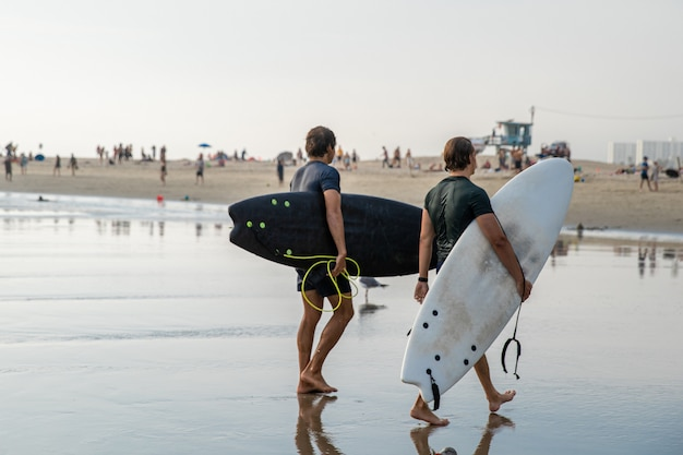 波でのアクティブなサーフィンの後、サーファーは海から戻ってきています