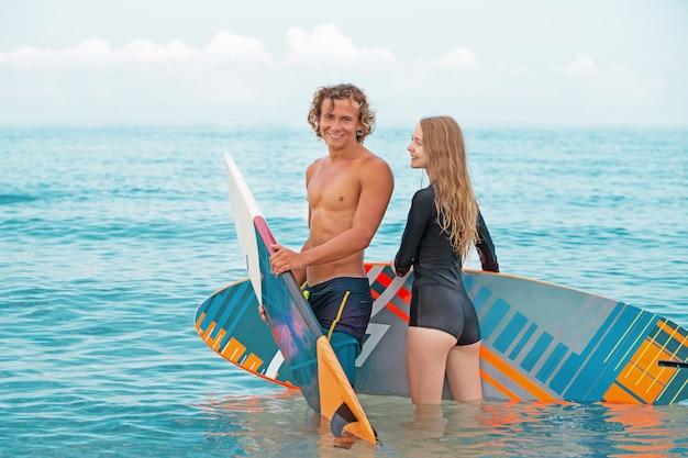 Surfers at the beach - пара улыбающихся серферов, гуляющих по пляжу и весело проводящих время летом. концепция экстремального спорта и отдыха