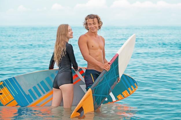 해변-서퍼 해변에서 걷고 여름에 재미 서퍼의 웃는 커플. 익 스 트림 스포츠 및 휴가 개념