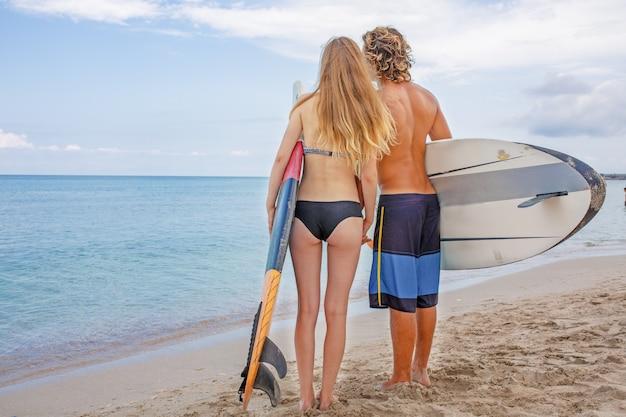 ビーチでサーファー-ビーチを歩いて、夏に楽しんでいるサーファーのカップルの笑顔。極端なスポーツと休暇の概念