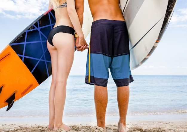 Surfers at the beach- smiling couple of surfers walking on the beach and having fun in summer. extreme sport and vacation concept