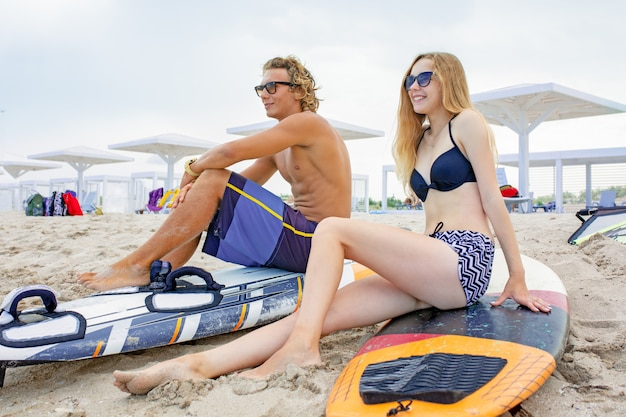 Surfers at the beach. smiling couple of surfers walking on the beach and having fun in summer. extreme sport and vacation concept