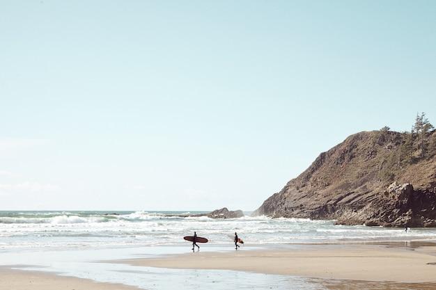 Серферы вдалеке на каменистом пляже
