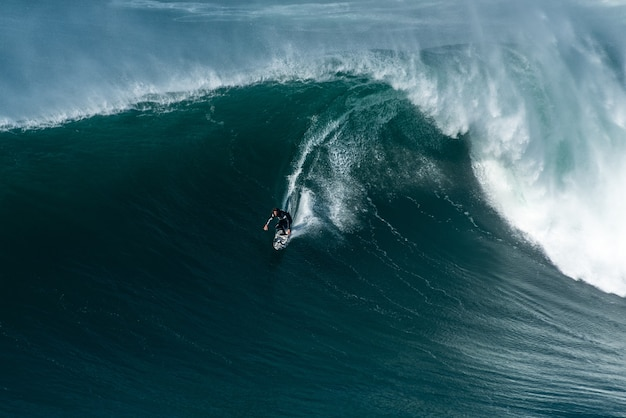 Surfers riding on the waves of the atlantic ocean toward the shore at nazare, portugal
