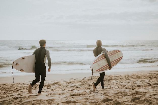 Серферы бегают по пляжу
