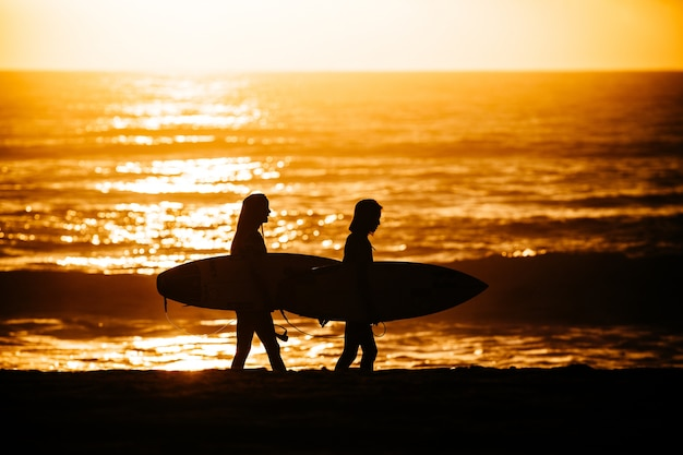 Surfers walking after an exhausting surfing session against a dazzling sunset background