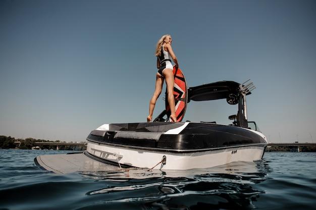 ボートの上に立ってサングラスでsurfgirl