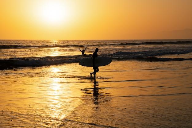 日没時のサーフィン。サーフボードを持つ男。アウトドアの人々のアクティブなライフスタイル。