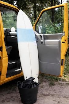 黄色いバンの横にあるサーフィンボード