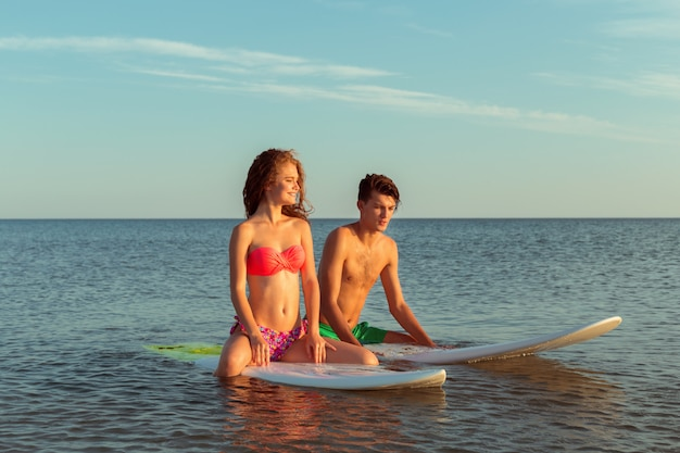 Surfing couple leaning on surfboards in sea