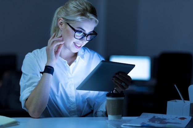새로운 아이디어를위한 서핑. 프로젝트에서 작업하는 동안 사무실에 앉아 태블릿을 사용하는 긍정적 인 매력적인 웃는 it 여자