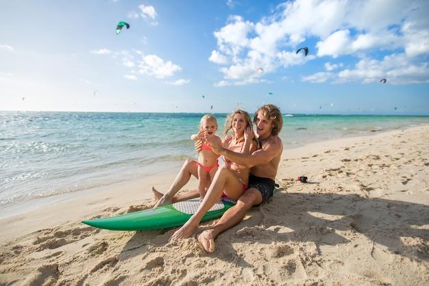 サーフィン。幸せな家族はサーフボードに座っています。家族、スポーツ、楽しみについての概念