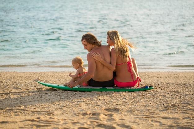 Серфинг. счастливая семья сидит на доске для серфинга. понятие о семье, спорте и развлечениях