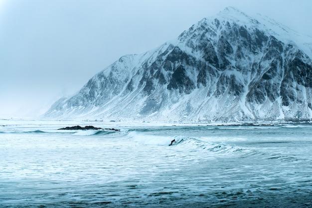 Серфинг на живописном арктическом пляже унстад на лофотенских островах в норвегии, известном месте для путешествий для серферов со всего мира. расположение - побережье норвежского моря, скандинавия, европа.