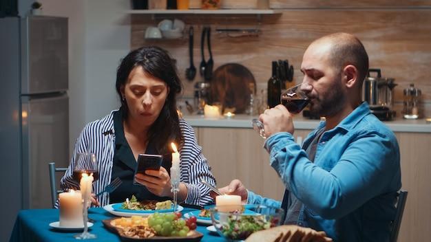 Navigare sui telefoni durante la cena coppia che tiene gli smartphone in cucina seduti al tavolo navigando, cercando, usando smartphone, internet, festeggiando il loro anniversario nella sala da pranzo.