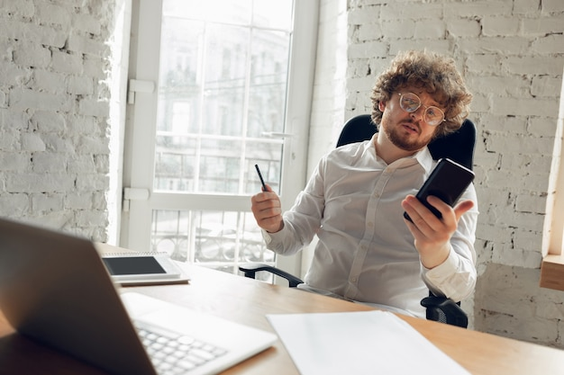 Surfing, reading. caucasian young man in business attire working in office. young businesswoman, manager doing tasks with smartphone, laptop, tablet has online conference. concept of job, education.