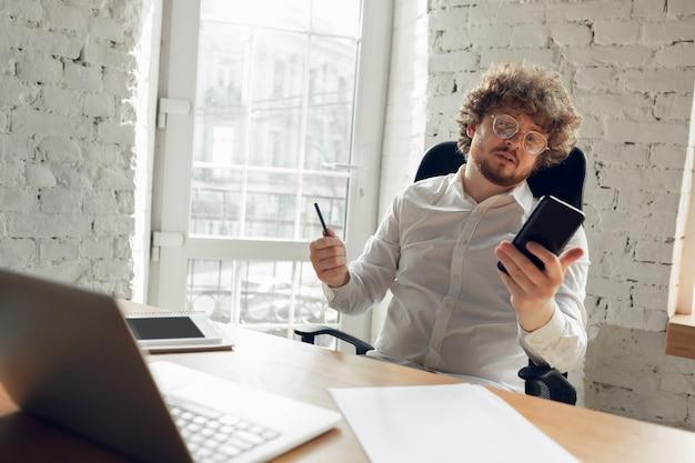 Серфинг, чтение. кавказский молодой человек в деловой одежде, работающих в офисе. молодой предприниматель, менеджер, выполняющий задачи со смартфоном, ноутбуком, планшетом, проводит онлайн-конференцию. понятие о работе, образовании.