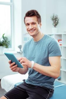 인터넷을 서핑. 그의 의사를 기다리는 동안 그의 새로운 태블릿을 들고 즐거운 젊은 남자