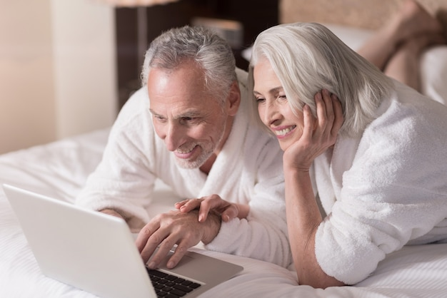 함께 인터넷 서핑. 쾌활한 미소 세 커플 침대에 누워 기쁨을 표현하면서 노트북에서 인터넷을 서핑