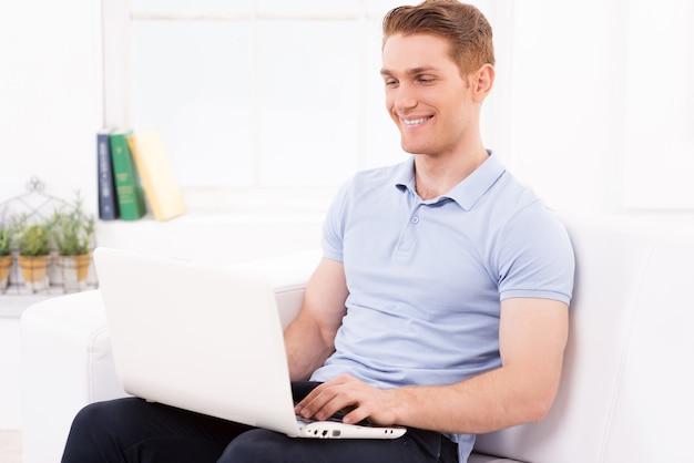 自宅でネットサーフィン。ソファに座ってラップトップで作業しているハンサムな若い男