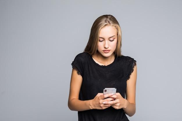 インターネットサーフィン。灰色の背景に立っている間笑顔でスマートフォンを使用して魅力的な若い女性