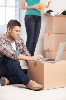 真新しい家でネットサーフィン。自信を持って若い男が床に座ってノートパソコンで作業している間、女性は背景のカートンボックスを開梱します。