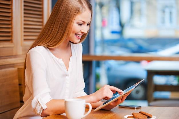 Серфинг в сети в кафе. вид сбоку красивой молодой женщины, использующей цифровой планшет и улыбающейся, наслаждаясь кофе в кафе