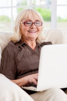 인터넷 서핑은 재미있습니다. 노트북 작업을 하고 의자에 앉아 웃고 있는 시니어 여성
