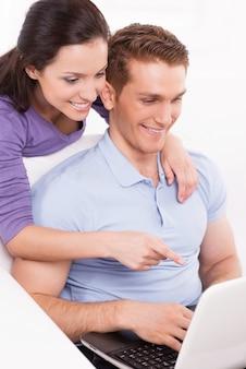 함께 인터넷 서핑. 행복한 젊은 부부는 소파에 앉아 노트북을 바라보며 모니터를 가리키며 웃고 있습니다.