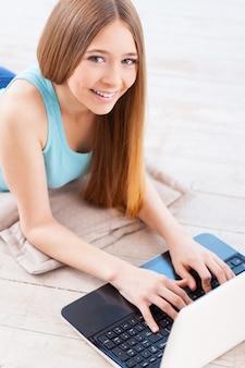 自宅でネットサーフィン。コンピューターを使用して、彼女のアパートの床に横になって笑っている陽気な若い10代の少女の上面図
