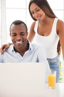 Surfing web together. beautiful young african couple looking at the laptop and smiling