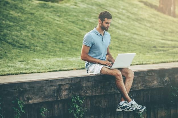 彼が望むところならどこでもネットサーフィン。波止場に座っている間ラップトップに取り組んでいるポロシャツのハンサムな若い男