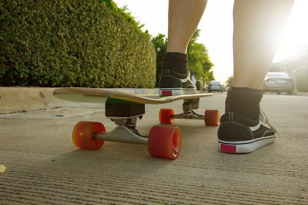 ニューノーマルのサーフスケートボード活動。ストリートカルチャーのスポーティーなティーンエイジャー。外でスケーターを練習。スケートボーダーはフリースタイルのモーションスタイルに備える。